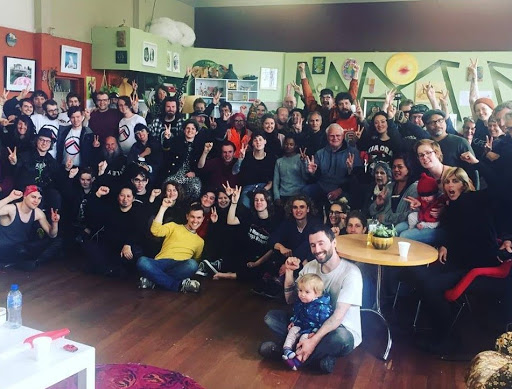 Community celebrates successful blockades of the weapons expo in Palmerston North, 2018. Group photo of about 50 people with raised fists.