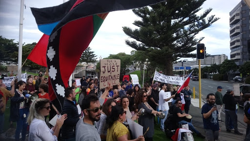 """Chilean community and supporters rally at Frank Kitts Park in Wellington. An indigenous Mapuche flag hangs in the frame and a man holds a sign which reads """"for a more just & equitable Chile."""""""
