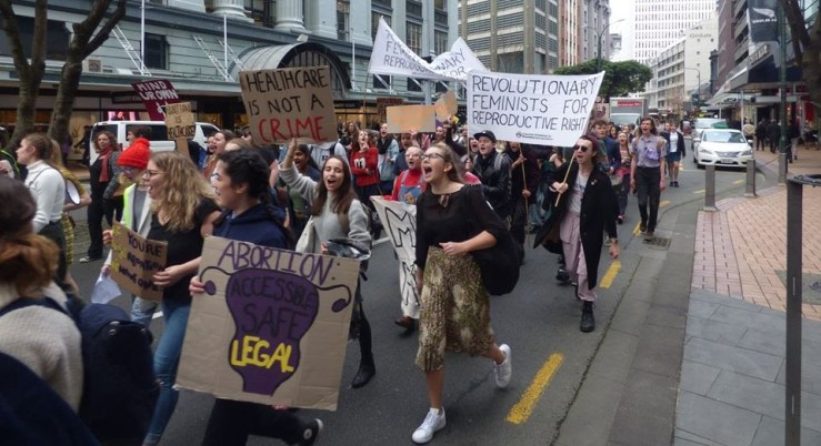 """March for abortion law refrom down Lambton Quay. OA members hold a banner which reads """"revolutionary feminists for reproductive rights."""" Other signs read """"Healthcare is not a crime"""" and """"abortion: accessible, safe, legal."""""""