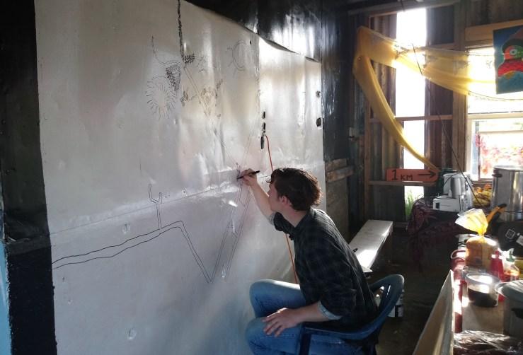 An OA member draws a map of Ihumātao on one of the walls in the wharekai.