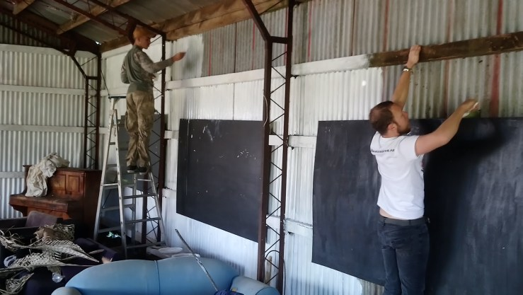OA members paint walls in the learning house at Kaitiaki Village.