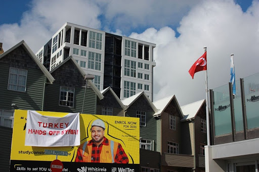 "Banner hangs on a billboard outside the Turkish Embassy in Wellington that reads ""Turkey Hands off Syria!"""
