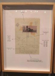 Inramat blad ur anteckningsblock, med ett litet fotografi och flera anteckningar runtomkring.