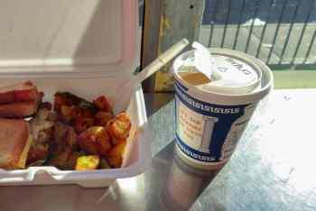 Frukost i en liten låda med en take away-mugg av grekiskt stuk bredvid.