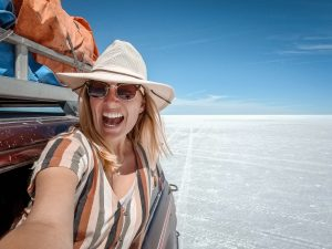 A woman leans out the window of a jeep in the white expansive salt flats of Uyuni in Bolivia.