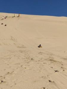Sand boarding down the dunes near Ninety Mile Beach