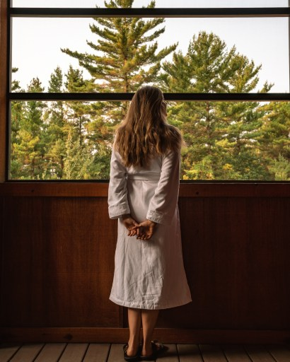 Four season porch view of the tree tops at Sundara Spa in Wisconsin Dells. A woman wears a white robe and enjoys the view.
