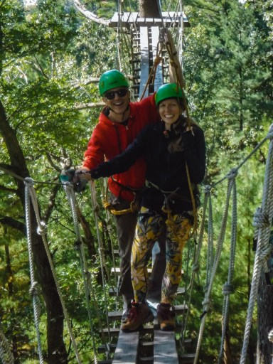 A couple on a ropes course bridge in the green forest of Wisconsin Dells just before fall.