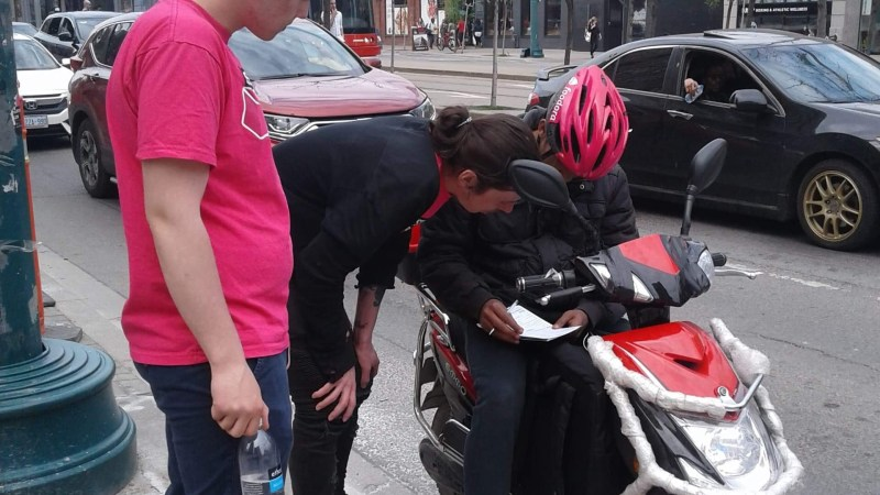 A Foodora worker signs a union card on their delivery bike