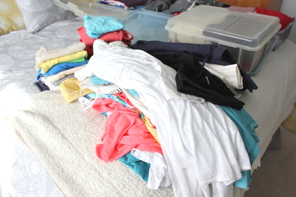 clothes piled on bed