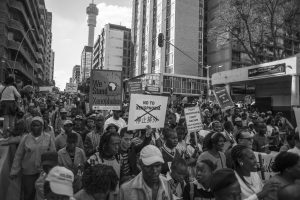 People hold up signs during a large anti-xenophobia rally in Johannesburg which was attended by thousands who marched through the city demanding an end to the violence against foreigners in South Africa.