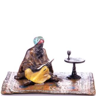 Farbige Bronzefigur lesender Gelehrte auf Teppich