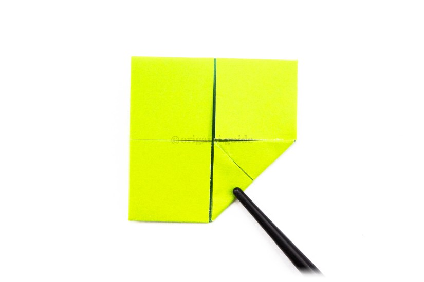 12. For a final time, fold a corner to the center of the paper.
