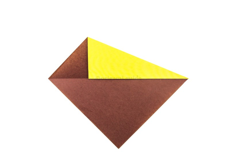 4. Take the top right diagonal edge and fold it down, aligning with the crease you made in step 2.