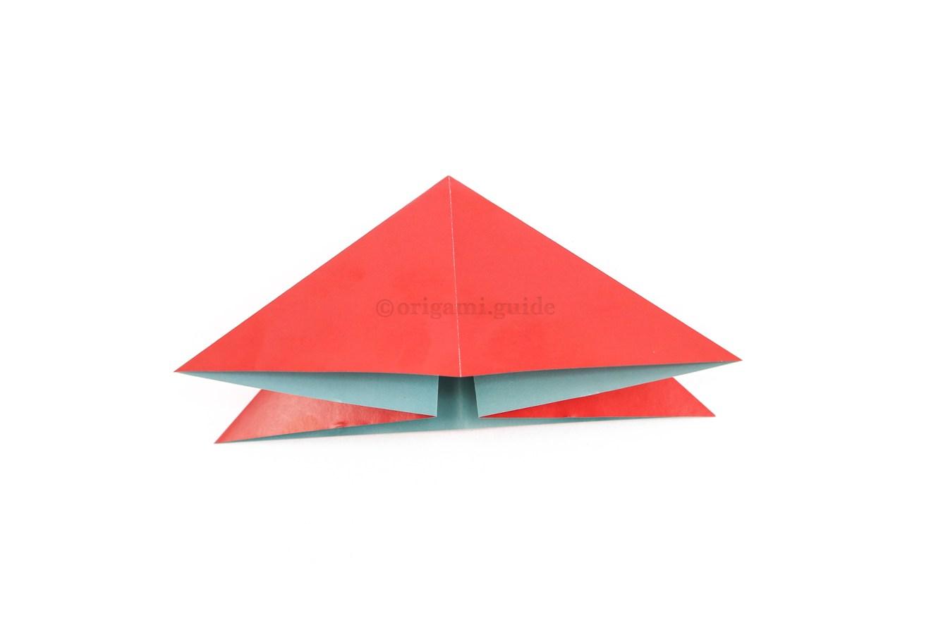 Flatten the paper into a triangular shape.
