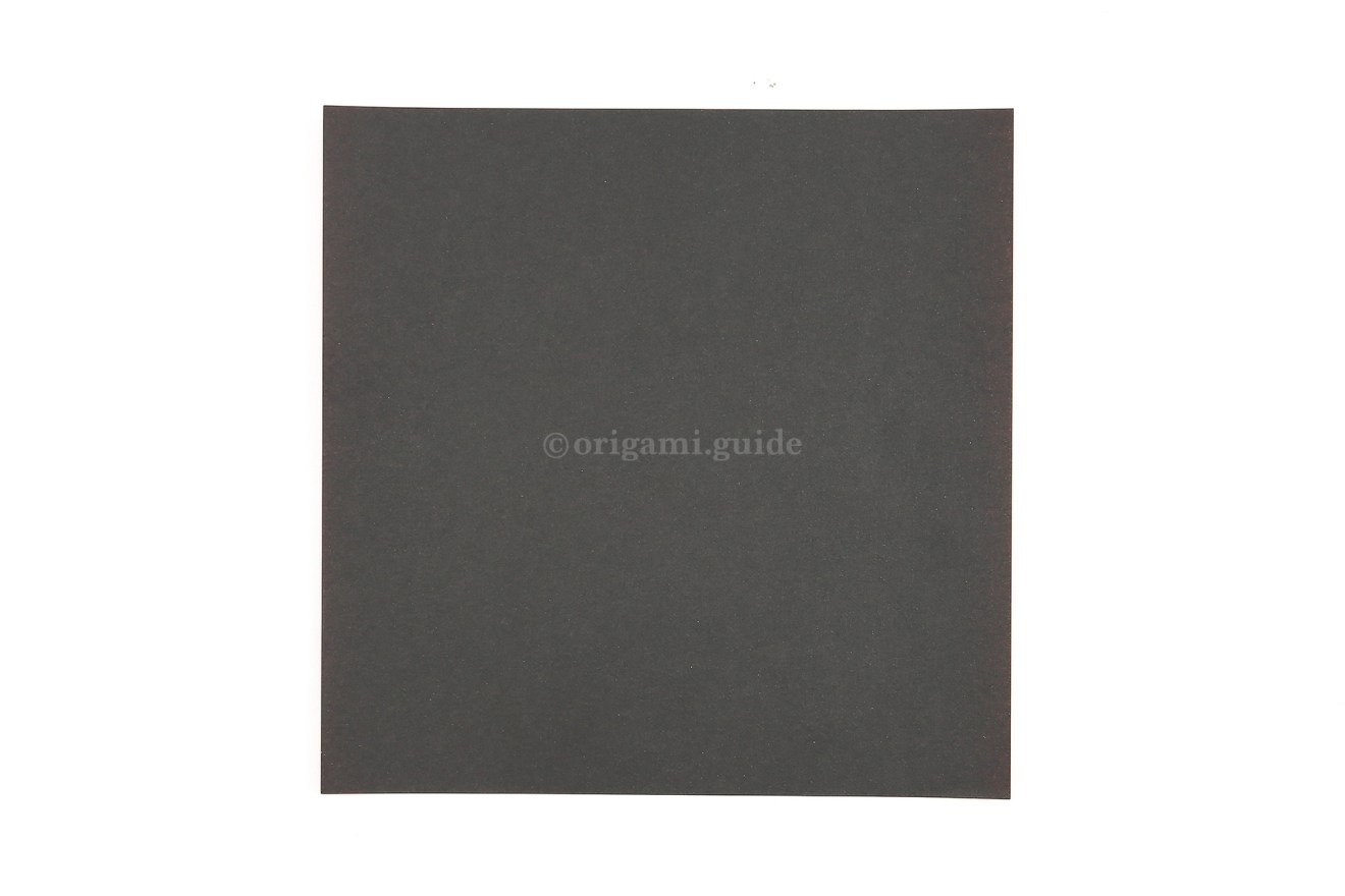 This is the front of our origami paper, our crow will be this colour, start this side up.