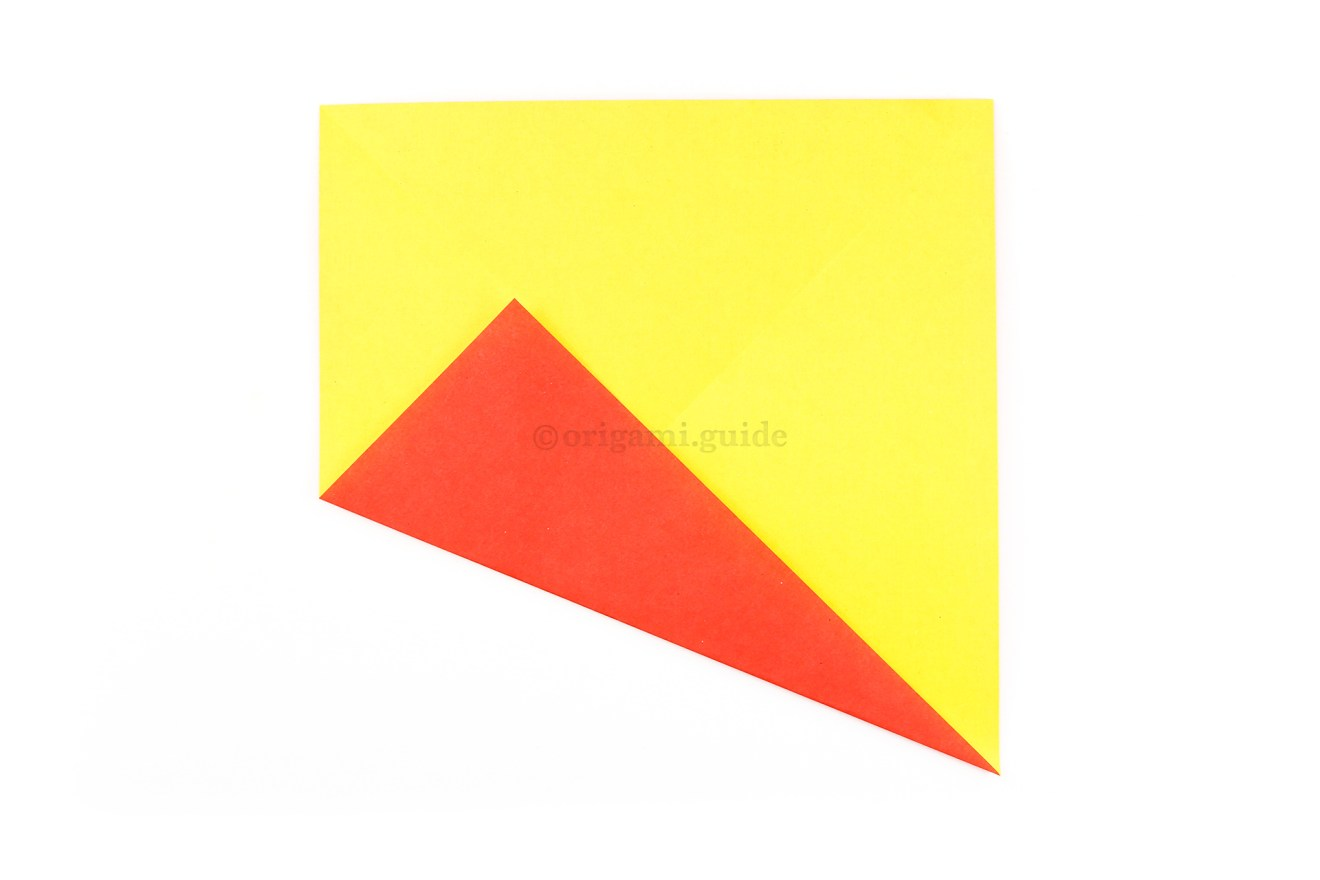 Fold the bottom left corner diagonally up to align with the central diagonal crease.