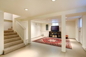 Basement Remodel with Central Beam and Posts and Living Room with Large Red Rug Beyond