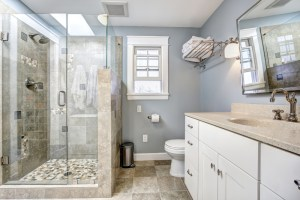 Bathroom Remodel with walk-in shower and toilet tucked around the vanity with stone, blue and white color palette
