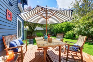 Exterior Remodel of 2-Story Painted Blue Siding House with Wood Deck in Lush Backyard