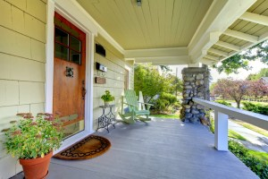 Exterior Remodel of Bungalow with Green Painted Siding, Deep Covered Front Porch, Stained Wood Front Door and Stone Columns