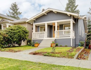 Exterior Remodel of Craftsman Bungalow with Painted Grey Siding, White Trim, White Railing and Stained Wood Door