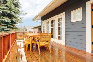 Exterior Remodel of Home with Painted Blue Siding, Double White Doors and Stained Wood Deck
