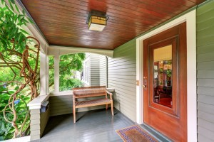 Exterior Remodel of Home with Painted Green Siding, Large Covered Front Porch and Stained Front Door