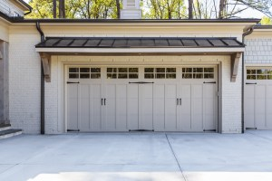 Garage Remodel with White Painted Brick and Cottage Style White Overhead Door with Large Awning above