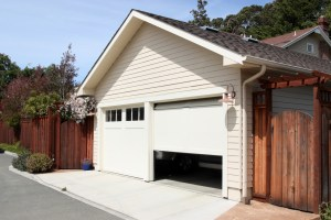 Garage Remodel with White Painted Siding, 2 Single Car Overhead Doors and Stained Wood Fence to Alley