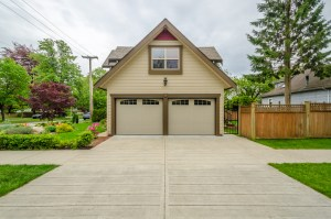 Garage with ADU Remodel with Painted Yellow Siding, Brown and Red Trim and 2 Single Car Overhead Doors