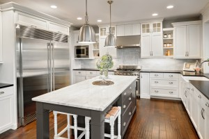 Kitchen Remodel with White Cabinets, Dark and Light Stone Countertops, Full Height Marble Tiled Backsplash, Farmhouse Sink and Hardwood Floor