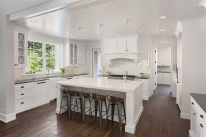 Kitchen Remodel with Inset Painted White Cabinets, Mixed Stone Countertops, and Full Height White Subway Tile Backsplash in this Open Floor Plan