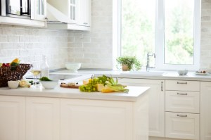 Kitchen Remodel with White Painted Cabinets, White Engineered Stone Countertops, Full Height Brick Tile Backsplash, Large Window to the Exterior at the Sink and Peninsula open to the Dining Room