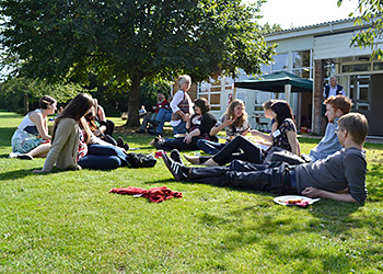 Singers enjoyed sitting and socializing on the green next to the Winnersh Community Centre Hall, where the UK Convention was held. Photograph by Ewan Paterson.