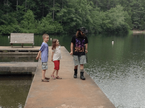 Faiz and Cora Wareh walk by the lake at Camp Lee with young adult camper Jackson Fleder. Photograph by Jonathon Smith.