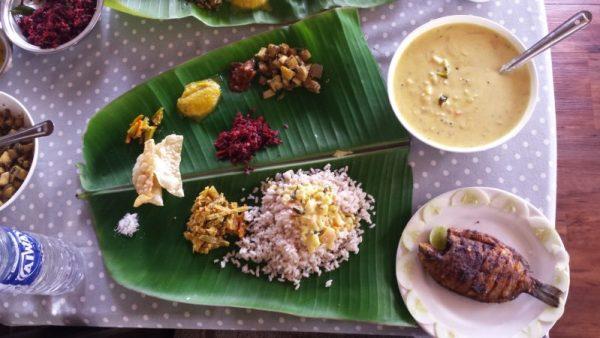 Tipica cucina del Kerala, curry, riso, pesce serviti su foglie di palma