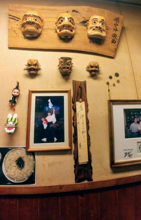 Maschere e foto sul muro del locale