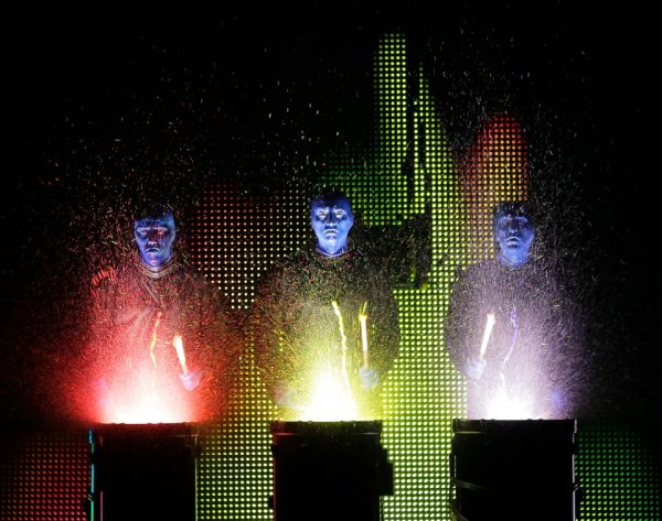 Blue Man Group Universal Orlando: image of three blue men hitting drums that glow with paint