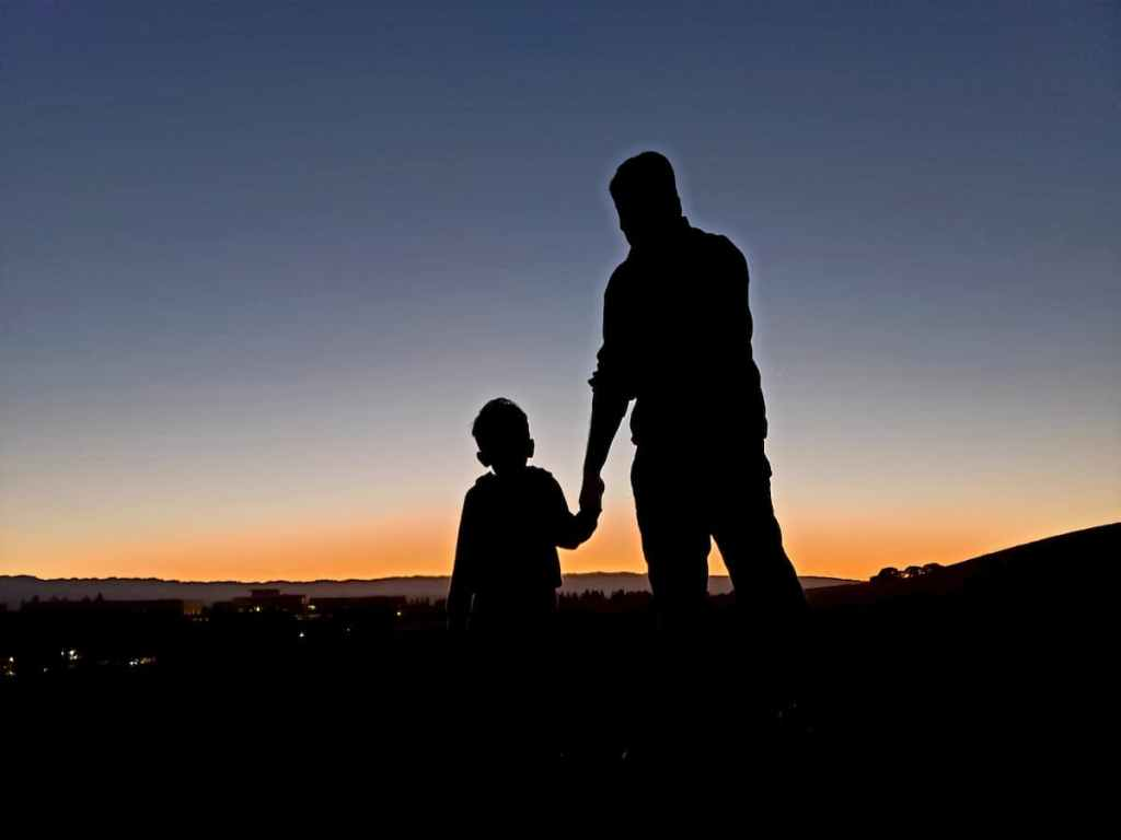 Silhouette of adult and child in front of a sunset