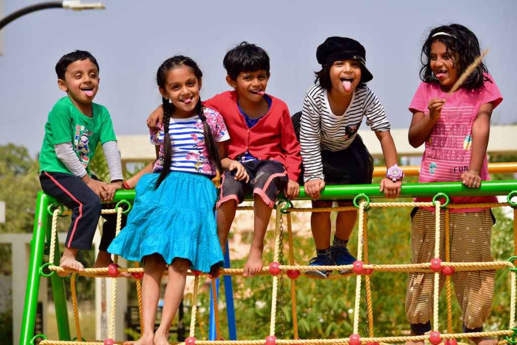 Children standing on a play structure.