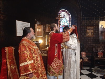 The aer is placed over the head of Deacon Aviv prior to his ordination as Priest