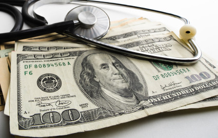 A stethoscope sits on top of a stack of U.S. cash money.