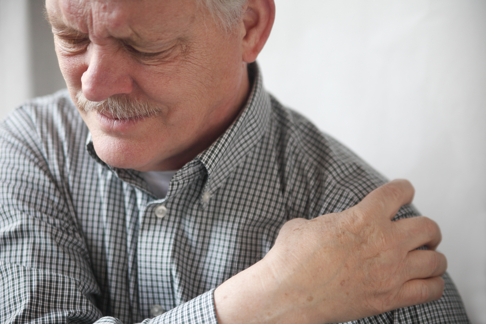 middle-aged man holding shoulder because of pain