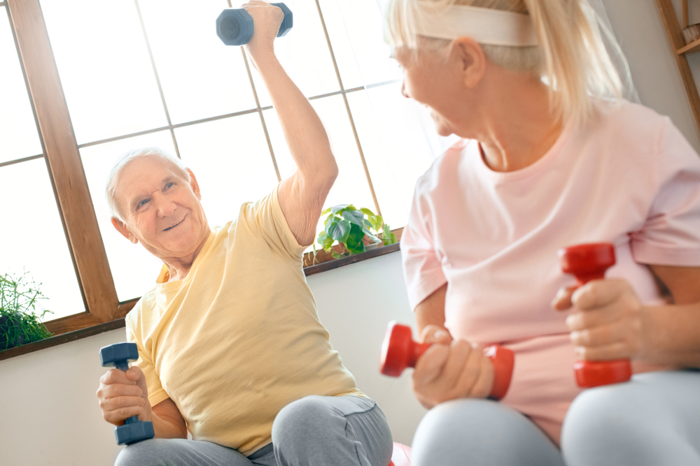 senior couple lifting dumbbells together at home