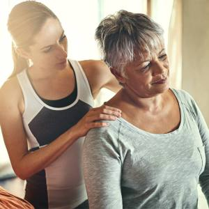 Neck pain can sometimes be relived by massage, younger woman works to loosen stiff muscles in neck and shoulder massage