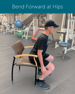 Orthopedic Institute Spine Therapist demonstrates proper sit to stand form by bending forward at the hips before rising to stand.