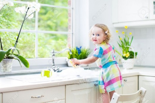 30781195-Cute-curly-toddler-girl-in-a-colorful-dress-washing-dishes-cleaning-with-a-sponge-and-playing-with-f-Stock-Photo