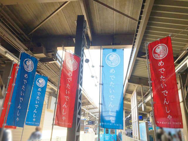 加太さかな線,駅にいくつかのめでたい電車ののぼりがかかっている様子,かい,水色の電車,南海電鉄,加太線,