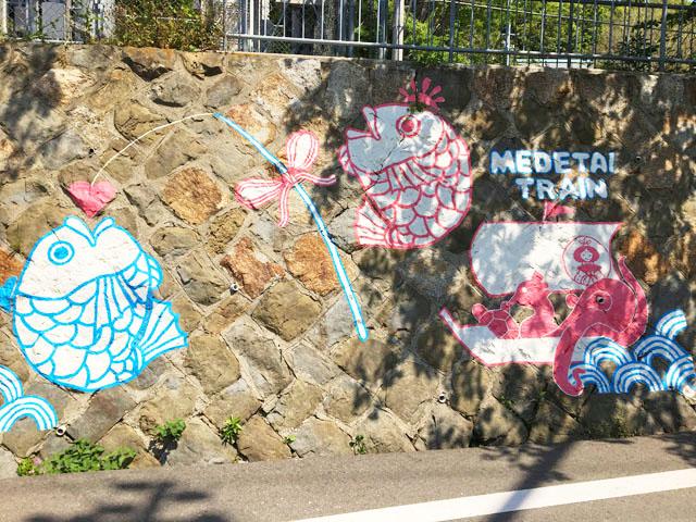 加太駅から加太港への通路の壁に「めでたいでんしゃ」のイラストが描かれている,